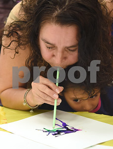 Maria Olivares helps her daughter Kamilah Olivares, 4, make a painting using a straw during the annual Art Gallery Walk at Bell Elementary School in Tyler Thursday. It was the 10th year for the event which features a piece of artwork from every student in the school.  (Sarah A. Miller/Tyler Morning Telegraph)
