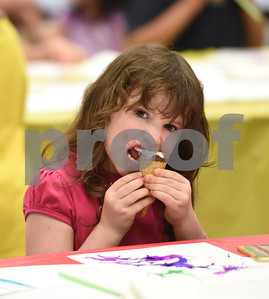 First grader Lydia Osteen eats ice cream during the annual Art Gallery Walk at Bell Elementary School in Tyler Thursday. It was the 10th year for the event which features a piece of artwork from every student in the school.  (Sarah A. Miller/Tyler Morning Telegraph)