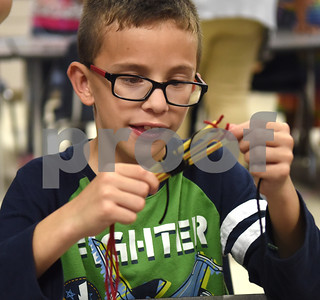 Second grader Alex Molina, 8, makes a friendship bracelet in the art room during the annual Art Gallery Walk at Bell Elementary School in Tyler Thursday. It was the 10th year for the event which features a piece of artwork from every student in the school.  (Sarah A. Miller/Tyler Morning Telegraph)