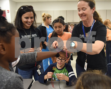 Art teacher Julianna Wynn ties a bracelet onto Makayla Taylor's arm during the annual Art Gallery Walk at Bell Elementary School in Tyler Thursday. It was the 10th year for the event which features a piece of artwork from every student in the school.  (Sarah A. Miller/Tyler Morning Telegraph)