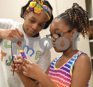Shantey Brown helps her daughter Caprielle Brown, 10, make a friendship bracelet in the art room during the annual Art Gallery Walk at Bell Elementary School in Tyler Thursday. It was the 10th year for the event which features a piece of artwork from every student in the school.  (Sarah A. Miller/Tyler Morning Telegraph)