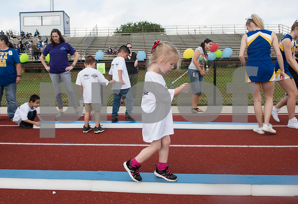 Students walk a balance beam during a Special Olympics Young Athletes event at Howard Cook Field in Jacksonville Friday April 21, 2017.    (Sarah A. Miller/Tyler Morning Telegraph)