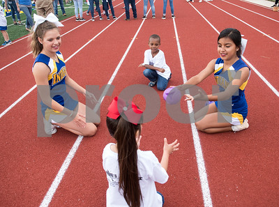 Jacksonville High School cheerleaders Mackenna Dement and Abby Hernandez play a game with Keystone Tilley, 5, and Evaney Suarez, 5, during a Special Olympics Young Athletes event at Howard Cook Field in Jacksonville Friday April 21, 2017.    (Sarah A. Miller/Tyler Morning Telegraph)