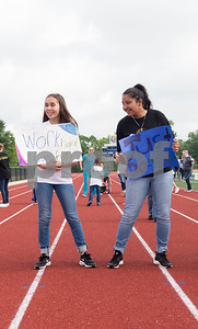 Jacksonville High School freshman Brandi Diaz and Amy Moreyra hold up encouraging signs for young athletes during a Special Olympics Young Athletes event at Howard Cook Field in Jacksonville Friday April 21, 2017.    (Sarah A. Miller/Tyler Morning Telegraph)