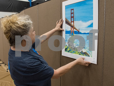 All Saints Episcopal middle school art teacher Linda Wheat hangs up a watercolor painting by eleventh grader Lilley Lewis during set up for the Student Art Exhibit Monday April 24, 2017. The art exhibit features pieces from all students grade 3K-12. It opens Tuesday at 6:30 p.m. at Brookshire Gym.  (Sarah A. Miller/Tyler Morning Telegraph)