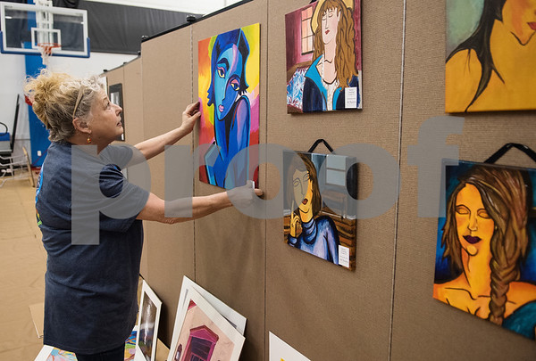 All Saints Episcopal middle school art teacher Linda Wheat hangs sets up for the Student Art Exhibit Monday April 24, 2017. The art exhibit features pieces from all students grade 3K-12. It opens Tuesday at 6:30 p.m. at Brookshire Gym.  (Sarah A. Miller/Tyler Morning Telegraph)