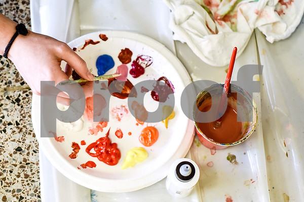 Art student Lauren Pitre mixes paint colors at the Biology, Education and Psychology building at The University of Texas at Tyler in Tyler, Texas, on Friday, April 28, 2017. The students started planning the mural in January and painting in February. (Chelsea Purgahn/Tyler Morning Telegraph)