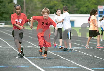 photo by Sarah A. Miller/Tyler Morning Telegraph  Andy Woods Elementary fifth graders Adreianna Rainey, 12, left, and Ben Bowman, 11, compete in the 1600 meter co-ed relay Tuesday at John Tyler High School. Andy Woods was one of four Tyler ISD schools whose fifth graders participated in track and field day.