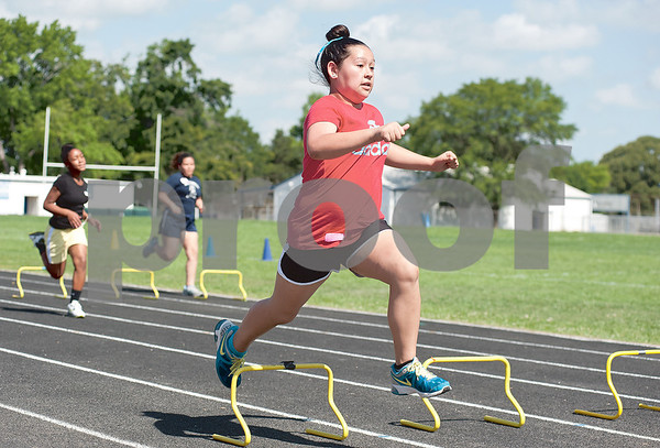 photo by Sarah A. Miller/Tyler Morning Telegraph  Andy Woods Elementary fifth grader Arivell Guzman, 11, runs the 100 meter hurdles Tuesday at John Tyler High School. Andy Woods was one of four Tyler ISD schools whose fifth graders participated in track and field day.