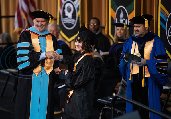 Tyler Junior College Chancellor and CEO Mike Metke shakes hands with Early College High School graduate Hannah McClellan as she receives her associates degree at the commencement ceremony for Engineering, Math & Science departments plus all Early College graduates on Friday May 10, 2019. This was the first class of Early College High School graduates.  (Sarah A. Miller/Tyler Morning Telegraph)