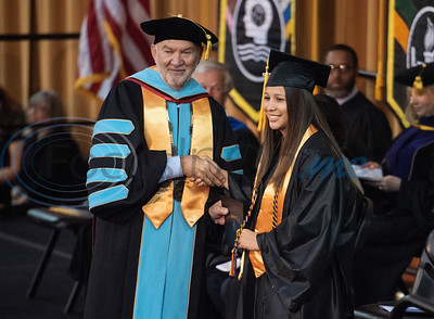 Tyler Junior College Chancellor and CEO Mike Metke shakes hands with Early College High School graduate Alex Urieta as she receives her associates degree at the commencement ceremony for Engineering, Math & Science departments plus all Early College graduates on Friday May 10, 2019. This was the first class of Early College High School graduates.  (Sarah A. Miller/Tyler Morning Telegraph)