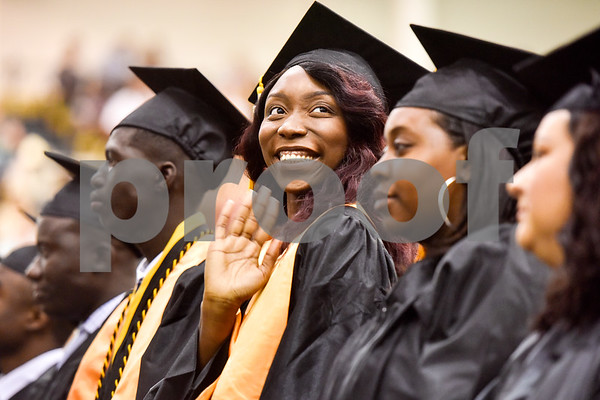 Sandoulena Mendy smiles and waves at friends and family during Tyler Junior College's spring commencement at Tyler Junior College in Tyler, Texas, on Friday, May 11, 2018. (Chelsea Purgahn/Tyler Morning Telegraph)