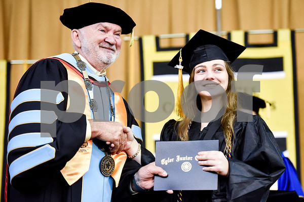 Chancellor and CEO Dr. Mike Metke shakes hands and poses for a photo with a graduate during Tyler Junior College's spring commencement at Tyler Junior College in Tyler, Texas, on Friday, May 11, 2018. (Chelsea Purgahn/Tyler Morning Telegraph)