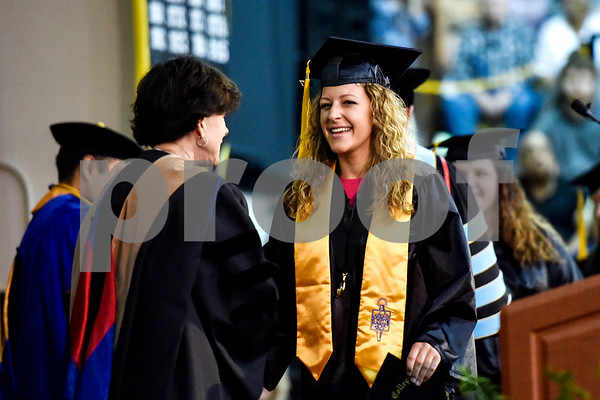 A graduate shakes hands with a faculty member during Tyler Junior College's commencement at Wagstaff Gymnasium in Tyler, Texas, on Friday, May 12, 2017. 1,141 students graduated in three different ceremonies. (Chelsea Purgahn/Tyler Morning Telegraph)