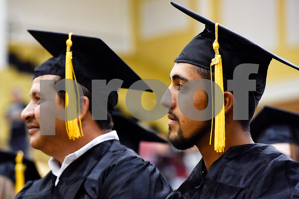 Father and son Edmundo and Levi Fuentes listen during a GED graduation ceremony at Wagstaff Gymnasium in Tyler, Texas, on Tuesday, May 16, 2017. Sixty-eight adult students walked the stage, with around 150 students total completing the program this year through Literacy Council of Tyler. (Chelsea Purgahn/Tyler Morning Telegraph)