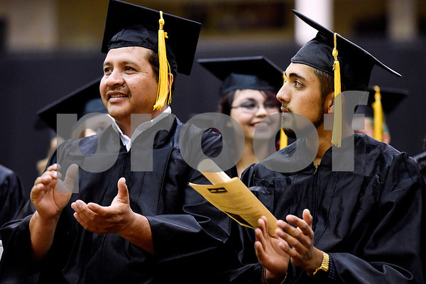 Father and son Edmundo and Levi Fuentes clap during a GED graduation ceremony at Wagstaff Gymnasium in Tyler, Texas, on Tuesday, May 16, 2017. Sixty-eight adult students walked the stage, with around 150 students total completing the program this year through Literacy Council of Tyler. (Chelsea Purgahn/Tyler Morning Telegraph)