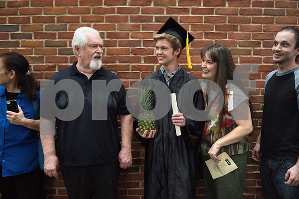 Graduate Donovan Furin of Tyler holds his graduation present- a pineapple, after the General Educational Development Commencement ceremony held Tuesday May 17, 2016 at Tyler Junior College's Wagstaff Gymnasium. Pictured at left is his grandfather Walter Starner and his mother Eve Brewer at right. The Literacy Council of Tyler, in partnership with TJC, provides GED preparation studies and pre-testing; English as a Second Language (ESL) and other programs.   (Sarah A. Miller/Tyler Morning Telegraph)