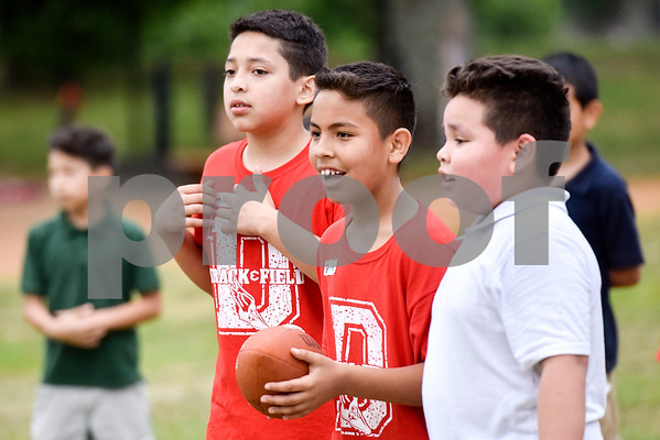 Boys play football during Sports Day hosted by Robert E. Lee students at Douglas Elementary School in Tyler, Texas, on Friday, May 19, 2017. The event was organized in part by teacher Mrs. Jones and her son Royland Black as a way to motivate and reward students for their hard work at the end of the school year. (Chelsea Purgahn/Tyler Morning Telegraph)