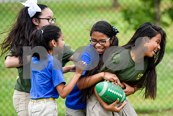 Girls laugh as they play football during Sports Day hosted by Robert E. Lee students at Douglas Elementary School in Tyler, Texas, on Friday, May 19, 2017. The event was organized in part by teacher Mrs. Jones and her son Royland Black as a way to motivate and reward students for their hard work at the end of the school year. (Chelsea Purgahn/Tyler Morning Telegraph)