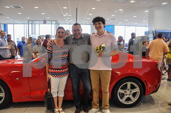 Peltier Enterprises Annual Teachers' Scholarship recipient and winner of the 2018 Chevrolet Camaro, Dylan Tucker (right) stops for a photo with his mom, Chandra Tucker (left) and Peltier Chevrolet General Manager, David Bates (middle) at the company's Annual Teachers' Scholarship on Saturday, May 19. For the first time since the inauguration of the Scholarship, a new 2018 Chevrolet Camaro was awarded at random to a scholarship recipient. (Jessica T. Payne/Tyler Paper)