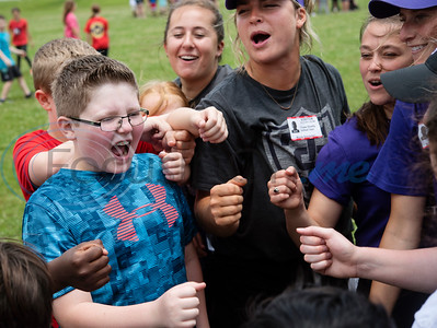 Andy Woods Elementary School fourth grader Taylor Isaac, left, gets in a huddle with members of the St. Thomas (Minn.) softball team as they start a game of kickball together at Pollard Park on Wednesday May 22, 2019. The St. Thomas team is in Tyler for the NCAA World Series which is being held at UT-Tyler starting on Thursday.  (Sarah A. Miller/Tyler Morning Telegraph)