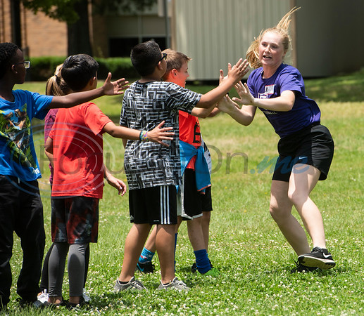 St. Thomas (Minn.) softball team player Sam Birling gives high-fives to fourth graders from Andy Woods Elementary School as the softball team plays kickball with the children at Pollard Park on Wednesday May 22, 2019. The St. Thomas team is in Tyler for the NCAA World Series which is being held at UT-Tyler starting on Thursday.  (Sarah A. Miller/Tyler Morning Telegraph)