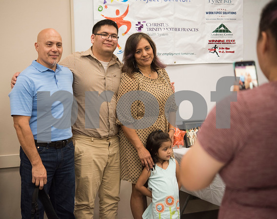 Project Search intern Daniel Palomo, center, has his photo taken his family including Daniel Palomo, Alma Soria and niece Janelle Chavez during the program's graduation ceremony on Friday May 25, 2018 at the Wisenbaker Conference Center at Christus Mother Frances Hospital in Tyler. Project Search is a partnership with Christus Trinity Mother Frances Health System, Tyler ISD, the Texas Workforce Solutions Vocational Rehabilitation Services, Winning Edge Employment Services, and the Andrews Center Behavioral Healthcare System that provides life skills and job training through internships for Tyler ISD students with disabilities.  (Sarah A. Miller/Tyler Morning Telegraph)