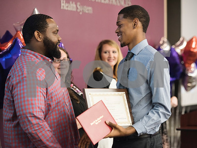 Project Search intern Zachariah Black, right, receives his program certificate of completion from job coach Kenneth Perkins during a graduation ceremony on Friday May 25, 2018 at the Wisenbaker Conference Center at Christus Mother Frances Hospital in Tyler. Project Search is a partnership with Christus Trinity Mother Frances Health System, Tyler ISD, the Texas Workforce Solutions Vocational Rehabilitation Services, Winning Edge Employment Services, and the Andrews Center Behavioral Healthcare System that provides life skills and job training through internships for Tyler ISD students with disabilities.  (Sarah A. Miller/Tyler Morning Telegraph)