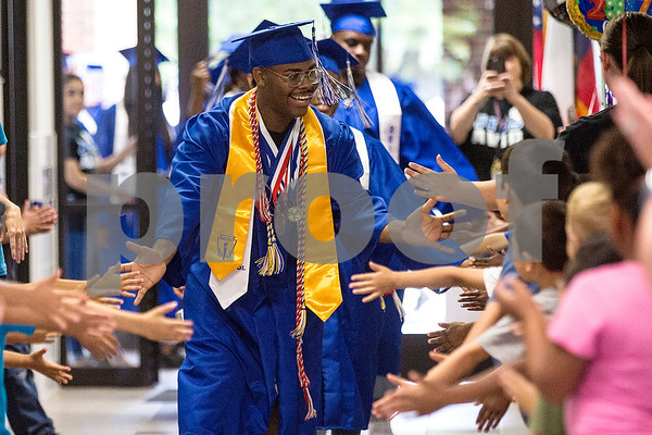 Donte Wilkerson high fives elementary students during a graduation walk honoring John Tyler High School seniors at Bell Elementary School in Tyler, Texas, on Friday, May 26, 2017. Graduating seniors participate in the event to inspire younger students to work hard and continue pursuing education. (Chelsea Purgahn/Tyler Morning Telegraph)