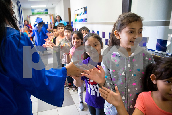 Elementary students give seniors high fives during a graduation walk honoring John Tyler High School seniors at Bell Elementary School in Tyler, Texas, on Friday, May 26, 2017. Graduating seniors participate in the event to inspire younger students to work hard and continue pursuing education. (Chelsea Purgahn/Tyler Morning Telegraph)