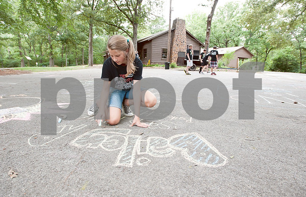 photo by Sarah A. Miller/Tyler Morning Telegraph  Sixth grader Bailey Richardson, 12, writes her name in chalk at Chapel Hill Middle School's Reward Day for UIL Academic students at Camp Tyler Outdoor School Wednesday. This was the third year for the camp which provides team building activities and games for sixth, seventh and eighth graders.