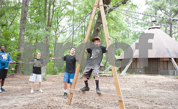 photo by Sarah A. Miller/Tyler Morning Telegraph  Sixth grader Brandon Sanchez, 12, depends on his classmates to help him balance inside an A-shaped wooden structure during a game called Walking A at Chapel Hill Middle School's Reward Day for UIL Academic students at Camp Tyler Outdoor School Wednesday. This was the third year for the camp which provides team building activities and games for sixth, seventh and eighth graders.