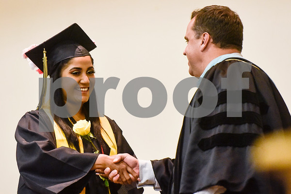 A graduate shakes Tyler ISD superintendent Dr. Marty Crawford's hand during Rise Academy's graduation at St. Louis Baptist Church in Tyler, Texas, on Thursday, May 31, 2018. Hundreds of family members and friends attended to see the 55 students graduate. (Chelsea Purgahn/Tyler Morning Telegraph)
