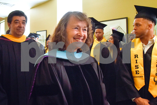 Tyler ISD board members Aaron Martinez and Patricia Nation walk by the graduates during Rise Academy's graduation at St. Louis Baptist Church in Tyler, Texas, on Thursday, May 31, 2018. Hundreds of family members and friends attended to see the 55 students graduate. (Chelsea Purgahn/Tyler Morning Telegraph)