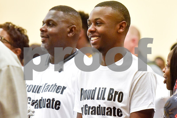 Marc and Kobe Walker stand as they watch the processional during Rise Academy's graduation at St. Louis Baptist Church in Tyler, Texas, on Thursday, May 31, 2018. Hundreds of family members and friends attended to see the 55 students graduate. (Chelsea Purgahn/Tyler Morning Telegraph)