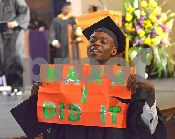 A recent Texas College graduate proudly displays a message to his mother on Saturday morning, during the 2013 Commencement Exercise. (Victor Texcucano)