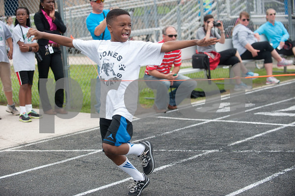 Jones Elementary School student Keyston Wilson, 9, raises his arms as he crosses the finish line in first place during a race at the fourth grade field day held at the John Tyler High School track Thursday May 7, 2015.   (photo by Sarah A. Miller/Tyler Morning Telegraph)