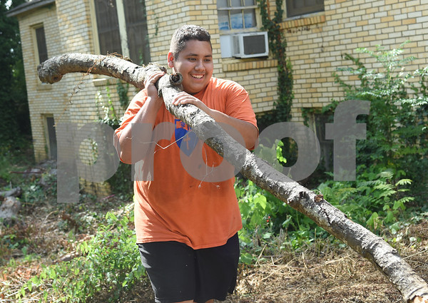 Kingdom Life Academy student Juan Uribe, 15, helps remove large tree branches from the yard of a home on Martin  Luther King Jr. Blvd. in Tyler Saturday morning June 11, 2016. The school has partnered with the City of Tyler to assist in yard work those who cannot do it themselves such as the elderly and disabled.   (Sarah A. Miller/Tyler Morning Telegraph)