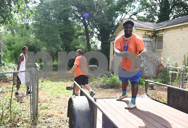 Kingdom Life Academy students Antione Neal, 18, Juan Uribe, 15, and Jaquan McKenzie, 17, help remove debris from trees from the yard of a home on Martin  Luther King Jr. Blvd. in Tyler Saturday morning June 11, 2016. The school has partnered with the City of Tyler to assist in yard work those who cannot do it themselves such as the elderly and disabled.   (Sarah A. Miller/Tyler Morning Telegraph)
