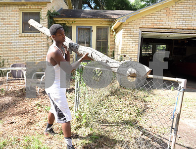 Kingdom Life Academy student Antione Neal, 18, helps remove large tree branches from the yard of a home on Martin  Luther King Jr. Blvd. in Tyler Saturday morning June 11, 2016. The school has partnered with the City of Tyler to assist in yard work those who cannot do it themselves such as the elderly and disabled.   (Sarah A. Miller/Tyler Morning Telegraph)
