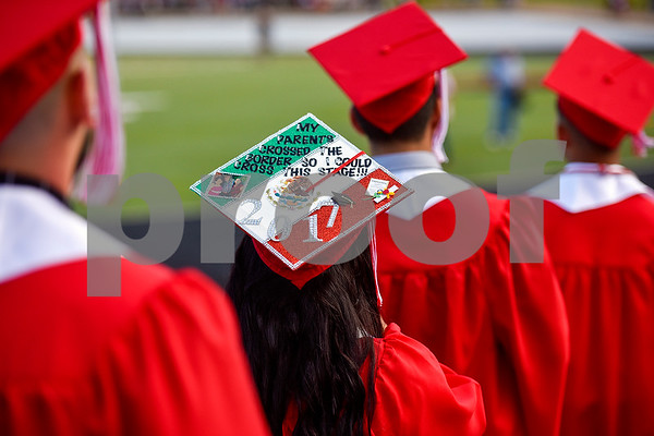 """Floribel Arroyo walks with other seniors as she wears a graduation cap that says """"My parents crossed the border so I could cross this stage!!!"""" during Robert E. Lee High School's graduation ceremony at Trinity Mother Frances Rose Stadium in Tyler, Texas, on Friday, June 2, 2017. Thousands of friends and family members came to see the hundreds of seniors walk the stage for graduation. (Chelsea Purgahn/Tyler Morning Telegraph)"""