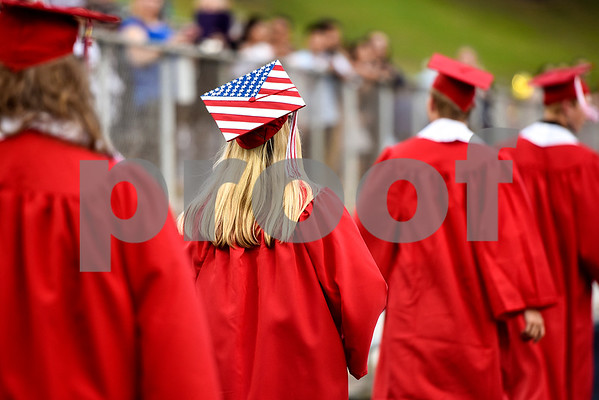 A senior with a cap decorated as an American flag walks with her peers during Robert E. Lee High School's graduation ceremony at Trinity Mother Frances Rose Stadium in Tyler, Texas, on Friday, June 2, 2017. Thousands of friends and family members came to see the hundreds of seniors walk the stage for graduation. (Chelsea Purgahn/Tyler Morning Telegraph)