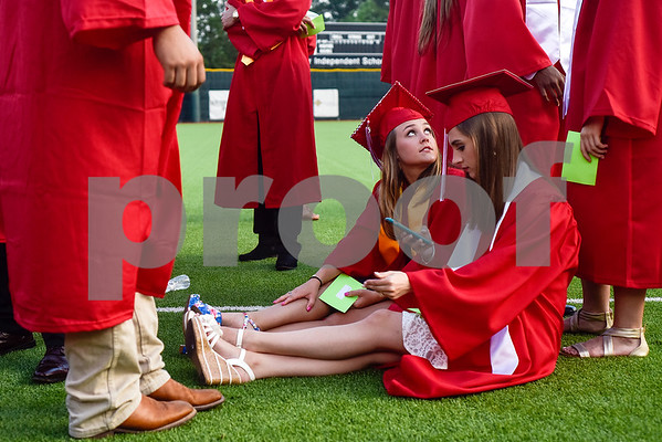 Shelby Kestler looks up at a friend as Amanda Hills looks at her phone before Robert E. Lee High School's graduation ceremony at Mike Carter Field in Tyler, Texas, on Friday, June 2, 2017. Thousands of friends and family members came to see the hundreds of seniors walk the stage for graduation. (Chelsea Purgahn/Tyler Morning Telegraph)