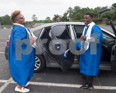 John Tyler High School students Pierre Leonard, Ladarrion Johnson and James Allen listen to music from a car stereo while putting their graduation gowns on before their high school commencement ceremony Friday night at Trinity Mother Frances Rose Stadium.  (Sarah A. Miller/Tyler Morning Telegraph)