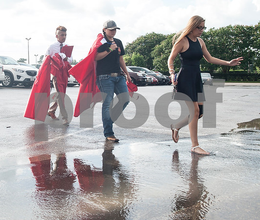 Robert E. Lee senior Doniel Paredo, junior Esperanza Vasquez and senior Shelby Gage doge parking lot puddles as they head to the staging area at Mike Carter Field Saturday night June 4, 2016. The commencement ceremony was held at the adjacent Trinity Mother Frances Rose Stadium.