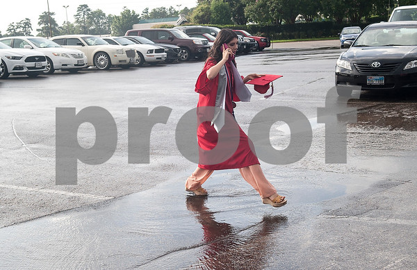 Robert E. Lee senior Gloria Rinconi walks over a puddle as she heads to the staging area at Mike Carter Field Saturday night June 4, 2016. The commencement ceremony was held at the adjacent Trinity Mother Frances Rose Stadium.