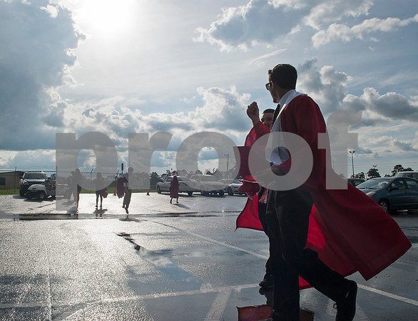 Robert E. Lee seniors are silhouetted against passing rain clouds as they wait at the staging area at Mike Carter Field Saturday night June 4, 2016 before their graduation. The commencement ceremony was held at the adjacent Trinity Mother Frances Rose Stadium.