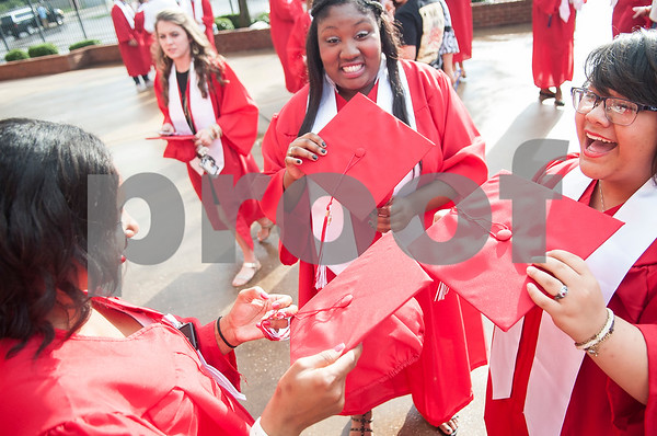 Robert E. Lee seniors Chelsey George, Lashaebrianna Smith and Abigail-Nykole Tidwell figure out the correct side for their cap tassels as they wait at the staging area at Mike Carter Field Saturday night June 4, 2016 before their graduation. The commencement ceremony was held at the adjacent Trinity Mother Frances Rose Stadium.  (Sarah A. Miller/Tyler Morning Telegraph)