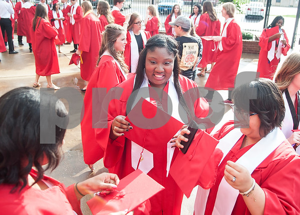 Robert E. Lee seniors Chelsey George, Lashaebrianna Smith and Abigail-Nykole Tidwell figure out the correct side for their cap tassels as they wait at the staging area at Mike Carter Field Saturday night June 4, 2016 before their graduation. The commencement ceremony was held at the adjacent Trinity Mother Frances Rose Stadium.