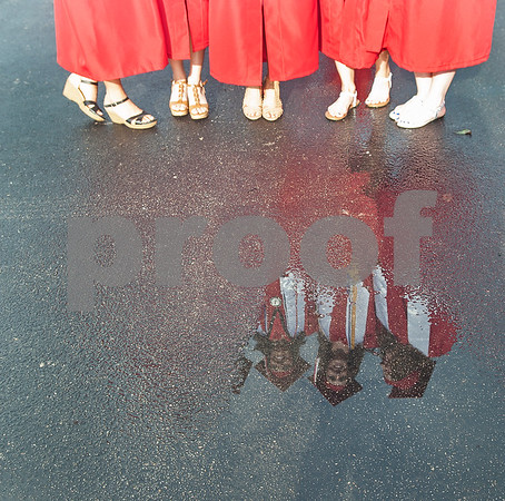 Robert E. Lee seniors are reflected in a puddle of water after a brief rainfall at the staging area at Mike Carter Field Saturday night June 4, 2016. The commencement ceremony was held at the adjacent Trinity Mother Frances Rose Stadium.